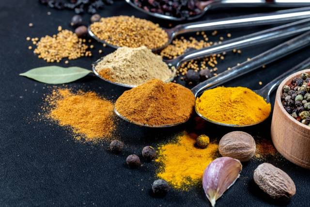 Close Up on spices on spoons - curcuma, curry, garlic, mustardseeds and barberries with nutmeg in front on black background