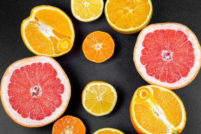 Fruit background with half a grapefruit, orange, lemon and mandarin on a black background, top view