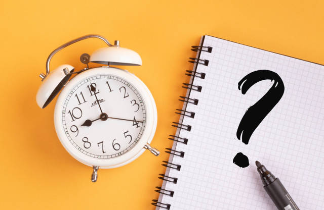 Alarm clock with question mark on yellow background