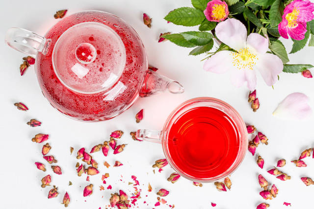 Beautiful tea background with rose flowers and freshly brewed tea in a teapot and cup on a white background, top view