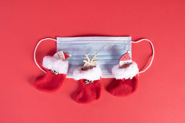 Medical face mask and christmas socks on red background