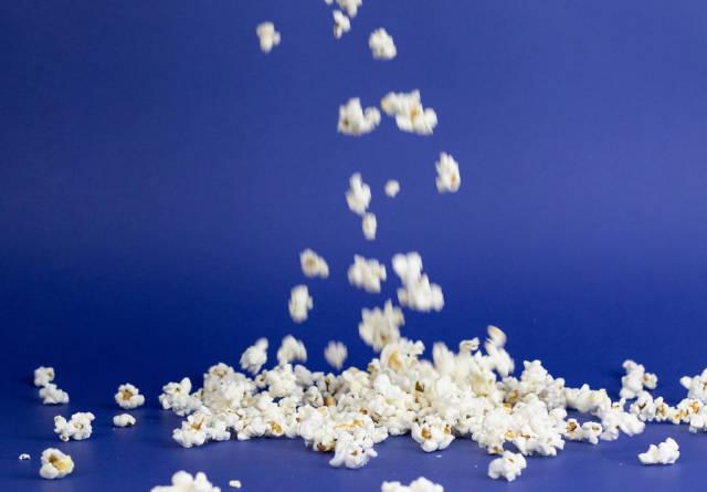 Fallende Popcorn vor blauem Hintergrund