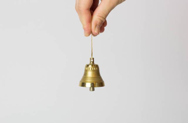Hand hält eine kleine Glocke