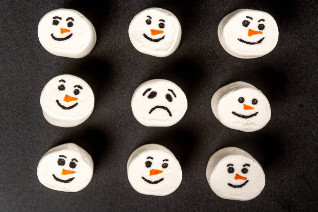 Top view, funny marshmallow emoticons and one sad on black background