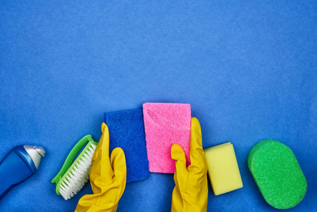 A rubber woman holds sponges over the cleaning products
