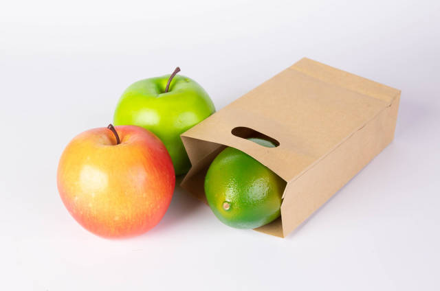 Paper bag with fruits on white background