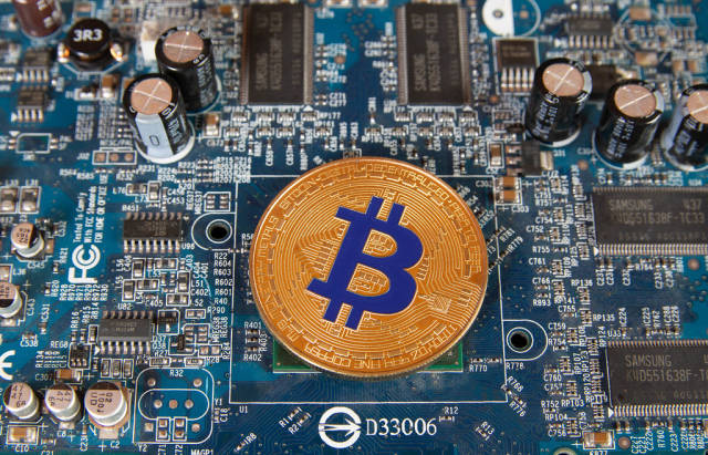 Golden Bitcoin on a computer mother board