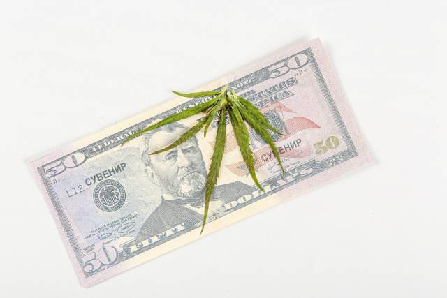 Green cannabis leaf on dollar bill, top view