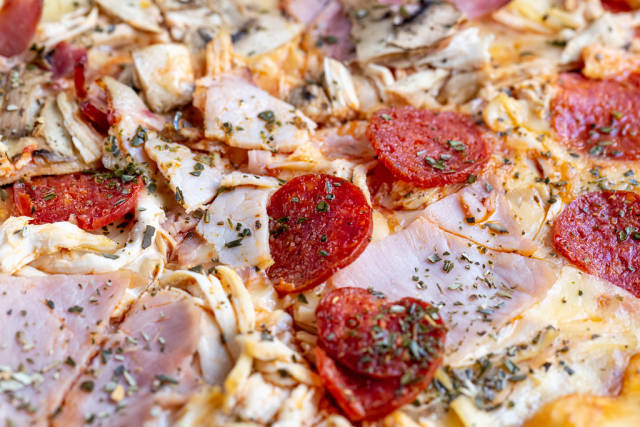 Pizza with smoked cured sausage close-up