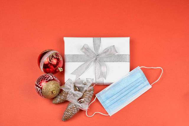 Christmas wrapped gift box, decorative items and face mask on red background