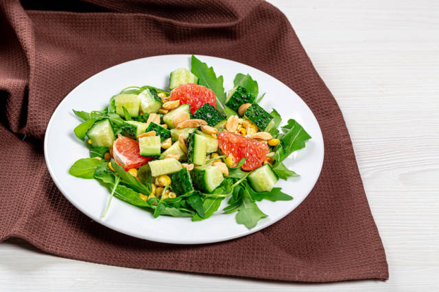 Salad with arugula, cucumbers, grapefruit and nuts on a white plate