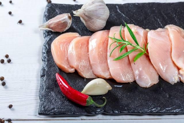 Mehrere Stücke rohe Hähnchenbrust mit Knoblauch, Chili, Rosmarin und Pfeffer auf Steinplatte