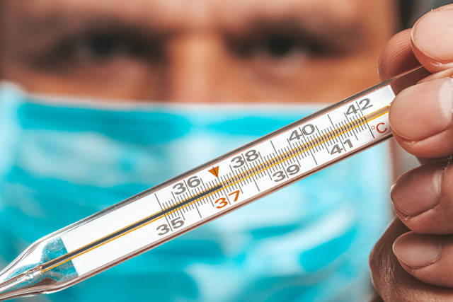 A man in a medical mask holding a thermometer