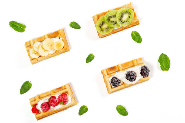 Delicious belgian waffles with pieces of fruits and berries on a white background with mint leaves