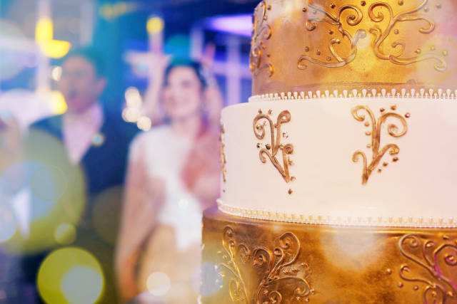 Wedding cake with bride and groom in the background