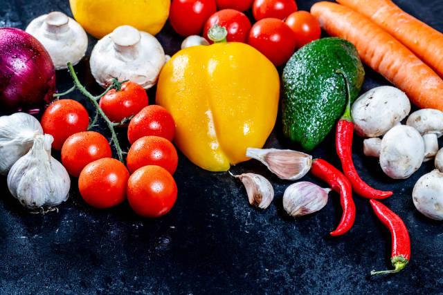 Konzept gesundes Essen mit frischem Gemüse wie Avocado, Paprika, Pilzen, Chilis und Knoblauch