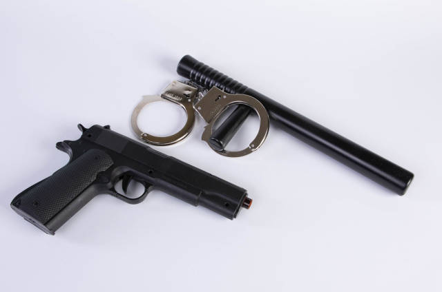 Handgun with rubber baton and handcuffs on a white background