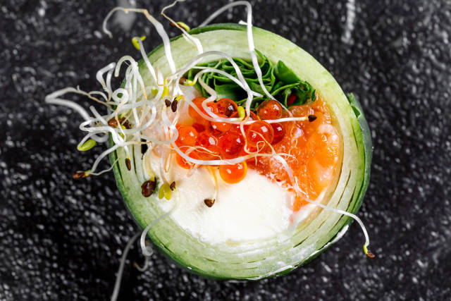 Roll with cucumber, salmon, cheese, arugula, micro greenery and red caviar on a black background. Top view