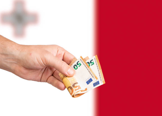 Hand with Euro banknotes over flag of Malta
