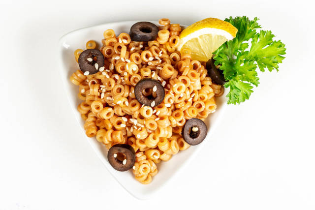 Boiled pasta with chunks of black olives, soy sauce and sesame seeds