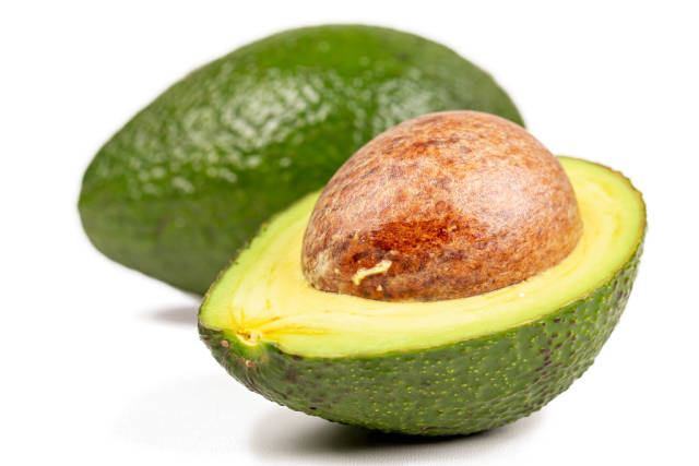 Close-up, half an avocado and a whole behind