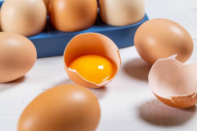 Raw broken chicken eggs on white background