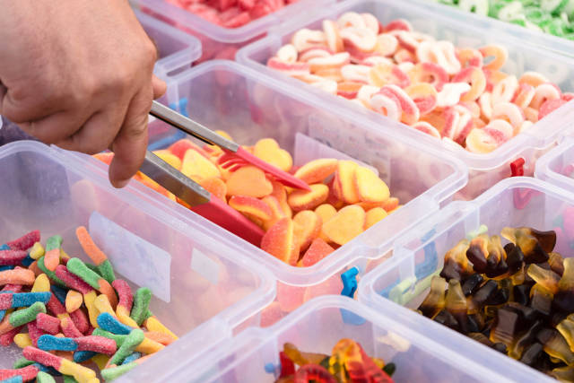 Picking Up the Gummy Jelly Sweets From The Plastic Container at the Market