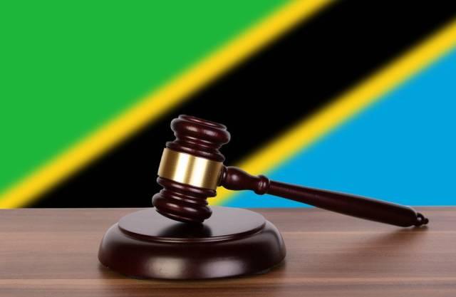 Auktionshammer / Richterhammer auf einem Holzuntergrund, vor der Flagge von Tanzania