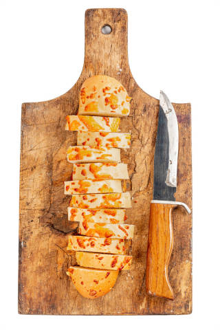 Sliced cheese baguette pieces on an old wooden board with a knife, top view