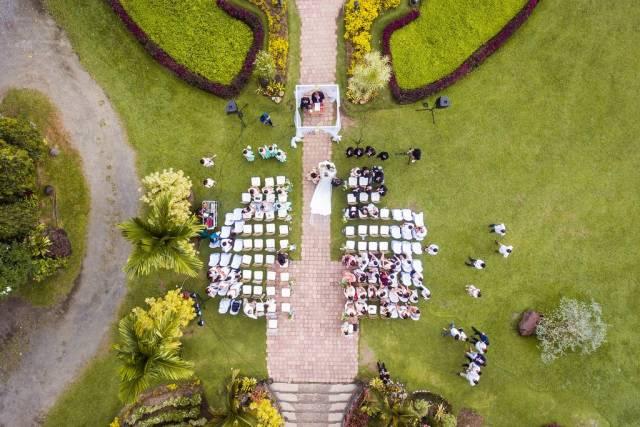 Drohnenaufnahme einer Hochzeit im Garten einer alten Villa, Brautpaar schreitet zum Traualtar