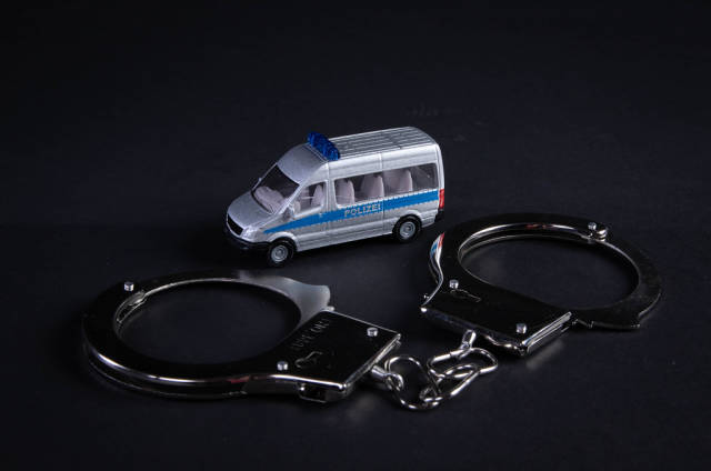 Metal handcuffs and police car on black background