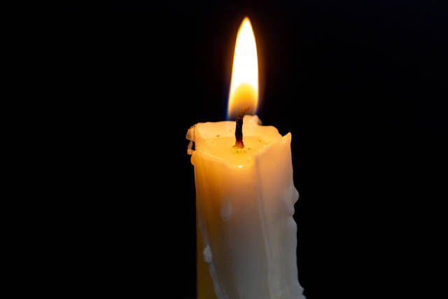 Candle burning brightly in the black background