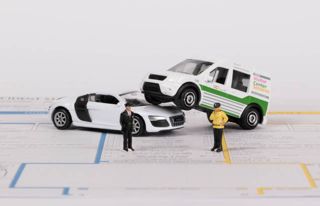 Two toy cars with policeman on accident statement report