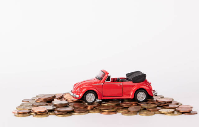 Red car over a lot of coins