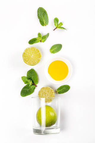 Top view of glass with lime, mint and honey on white background, beverage preparation concept