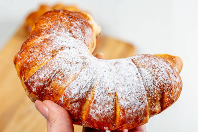 Bagel with powdered sugar in a womans hand