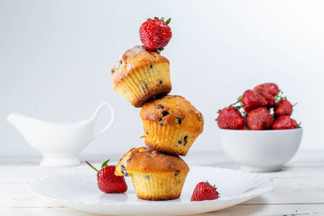 Muffins with chocolate pieces and fresh strawberries