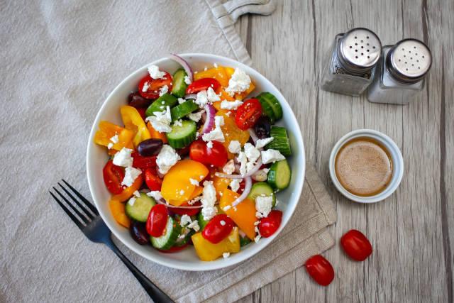 Griechischer Salat mit Cherrytomaten, Paprika, Gurke, Zwiebel, schwarzen Oliven und Fetakäse. Draufsicht
