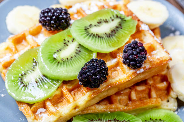 Slices of kiwi and banana with mulberry on Belgian waffles close-up