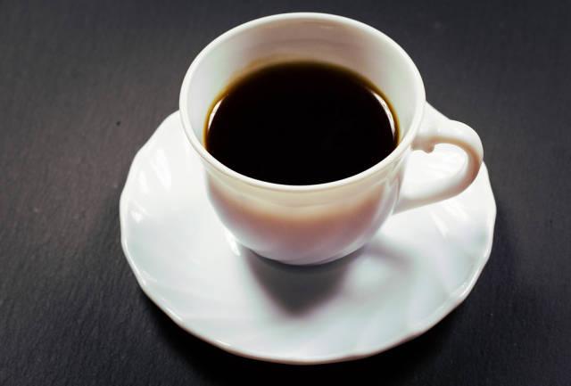 Tasse Kaffee vor einem schwarzen Hintergrund