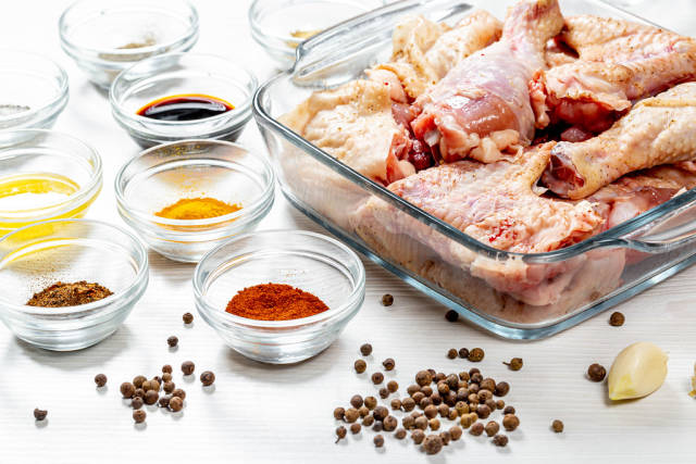 Raw chicken with spices on a white wooden table. Home cooking concept