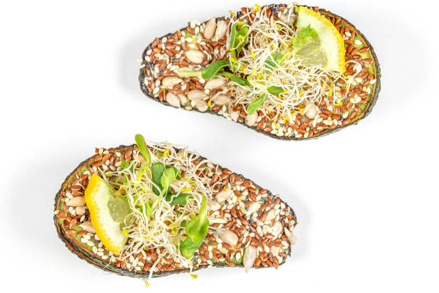 Avocado halves stuffed with microgreens and a mixture of seeds, top view