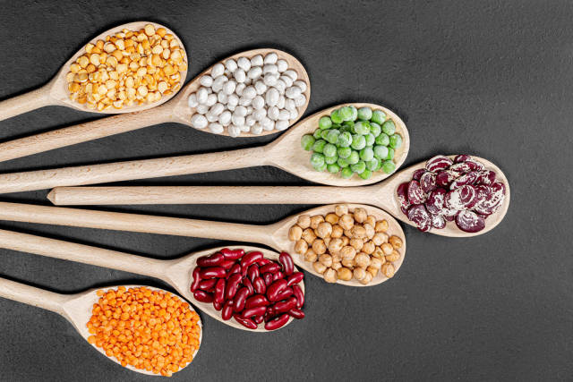 Lentils, chickpeas, peas and beans of different colors in wooden spoons on a black background. Top view