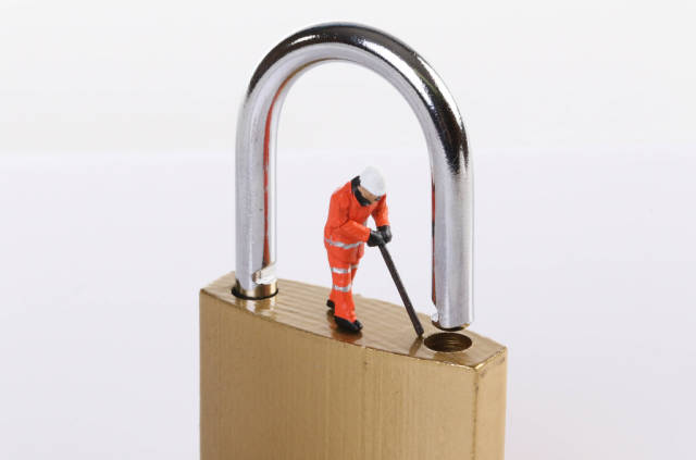 Miniature worker trying to unlock the padlock