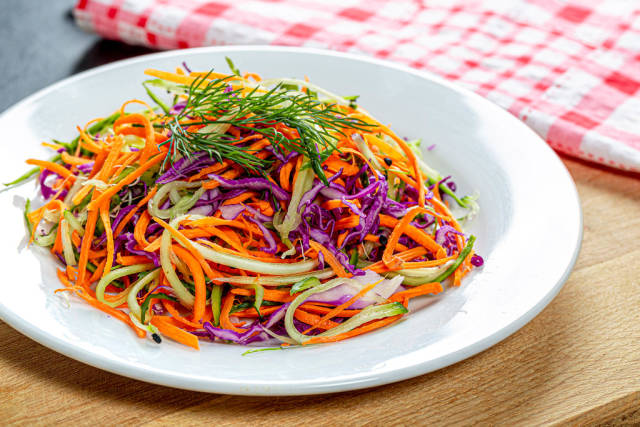 Fresh salad with carrots, cucumber and purple cabbage on a white plate