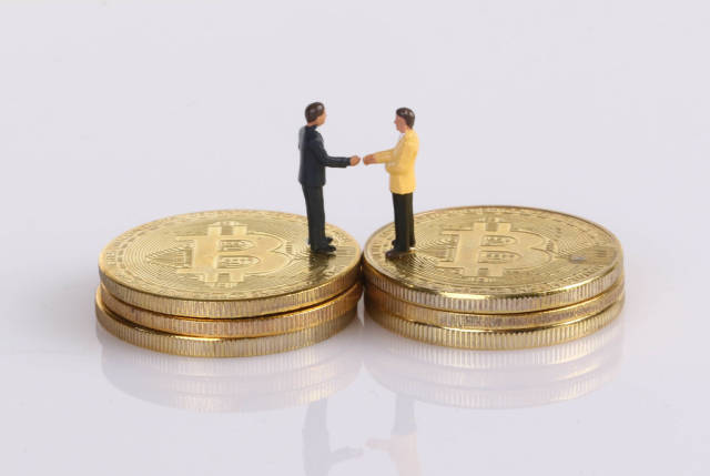 Two businessman shaking hands while standing on golden Bitcoins