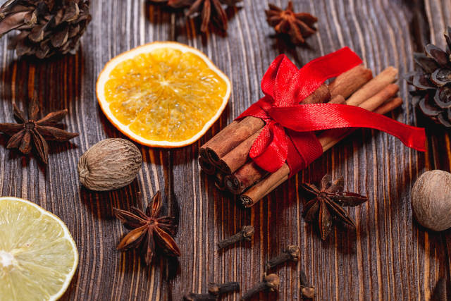 Traditional winter spices: anise, cinnamon, cloves and nutmeg with dried lemon and orange slices on a brown wood background