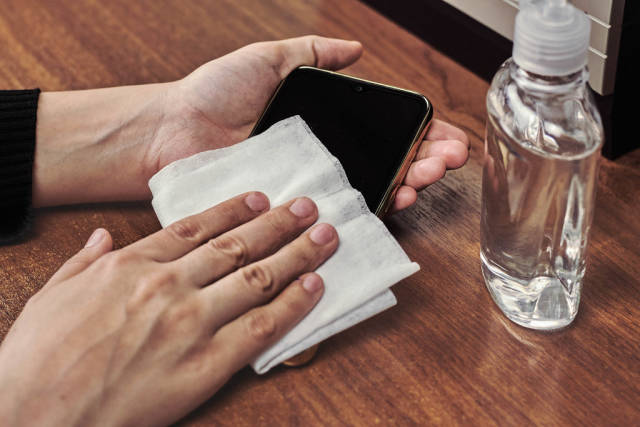 Woman cleaning smartphone with wet wipe at wooden table