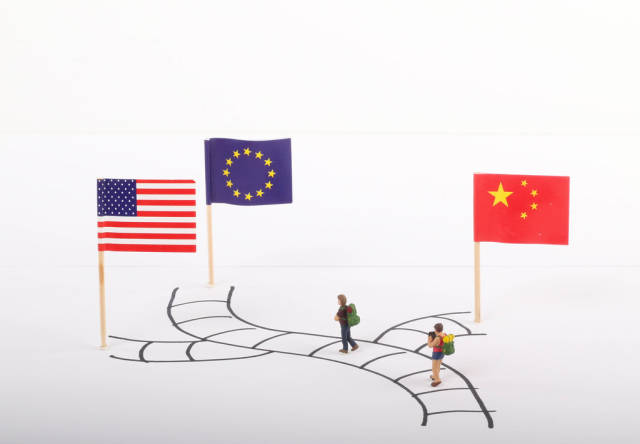 Two travelers standing on path with flags of USA, European Union and China
