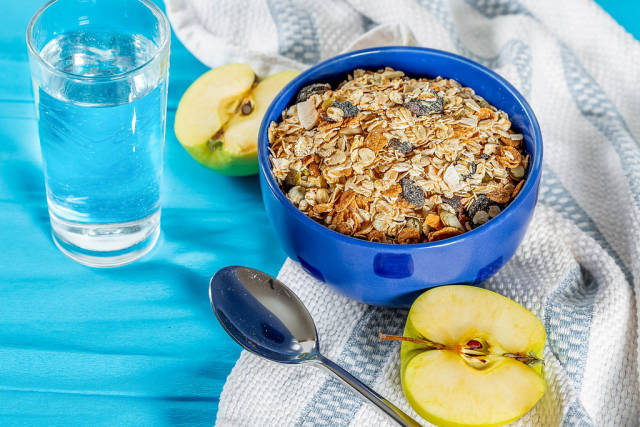 Oatmeal porridge with nuts and dried fruits and a glass of water-Breakfast during the diet